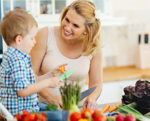 Mother and child preparing lunch in kitchen