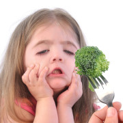 A young girl is making a funny disgusting face at a fork with a healthy piece of broccoli on a white background.